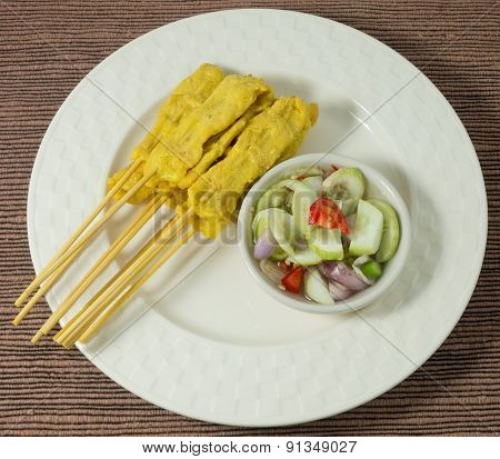 Grilled Pork Satay With Cucumber Salad On White Dish