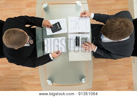 Two Businessman Calculating Bills Using Calculator