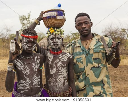 Boys From Mursi Tribe And A Solder With Machine Guns In Mirobey Village. Omo Valley. Ethiopia.