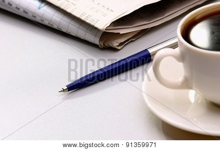 Cup of coffee, pen and newspapers on the desk