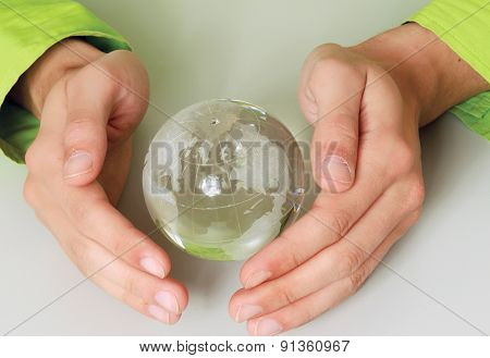 Male hands holding paper people around a glass globe