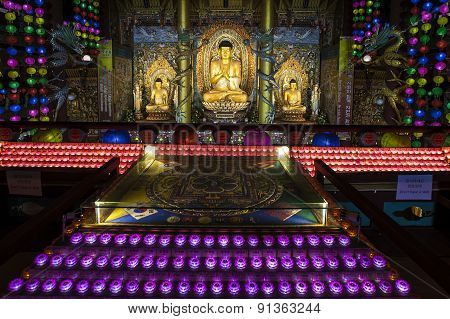 Colored lights illuminate Golden Buddhas at Yakcheonsa Buddhist Temple