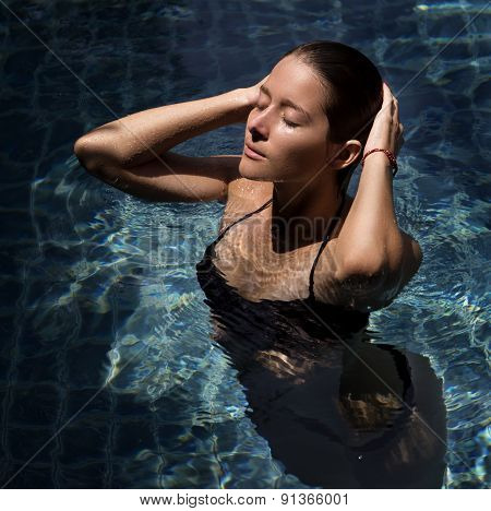 female model posing by the pool