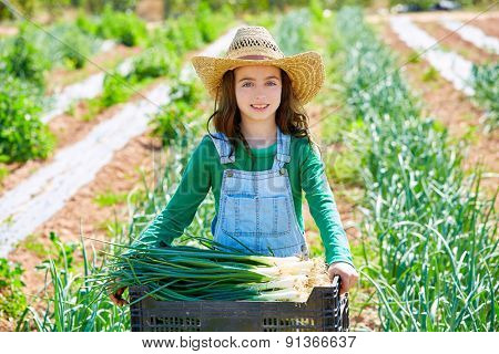 Little kid farmer girl in onion harvest at orchard