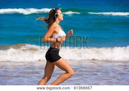 Brunette girl running on the beach with headphones