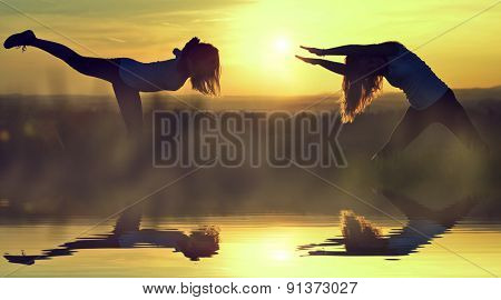 Silhouette girls stretching on a meadow at sunset