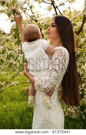Beautiful Mother Posing With Her Little Cute Baby In Blossom Garden