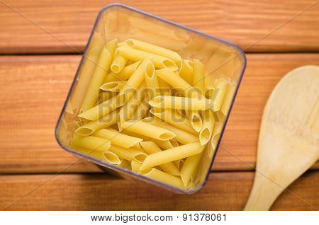 pasta in a transparent container with wooden spoon