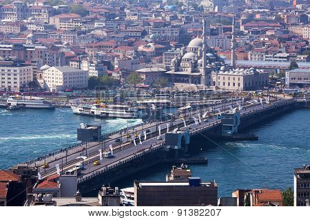 ISTANBUL, TURKEY - MAY 14 2015 : Traffic crosses over the Galata Bridge and boats pass under.