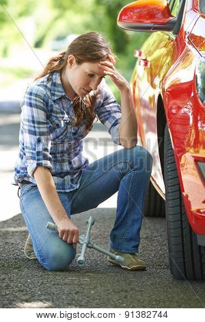 Frustrated Female Driver With Tyre Iron Trying To Change Wheel