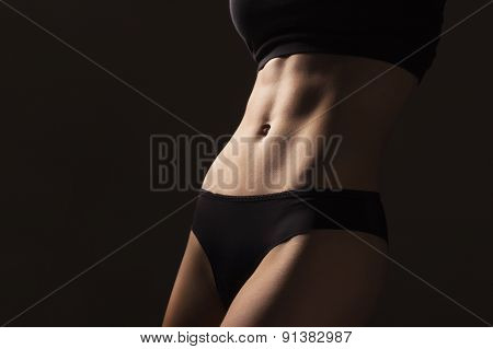 Sexy Slim Fit Woman Body. Muscled Abdomen. Sportswear. Belly And Legs. Dark Background