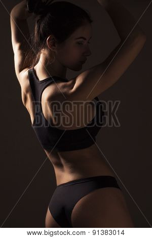Sexy Slim Fit Woman Body. Muscled Back. Sportswear. Dark Background