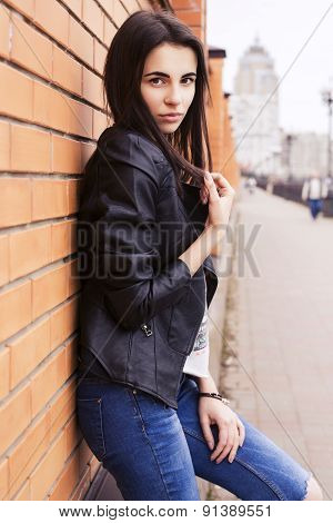 beautiful brunette woman in black leather jacket sitting on the embankment