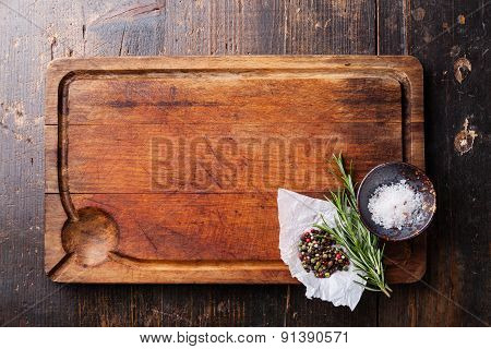 Chopping Board, Seasonings And Rosemary On Dark Wooden Background
