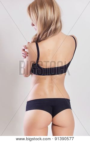 Sexy Slim Fit Blonde Woman In Sportswear. Muscled Back. Neutral Light Grey Background