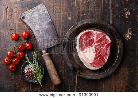 Raw Fresh Cross Cut Veal Shank For Making Osso Buco And Meat Cleaver On Dark Wooden Background