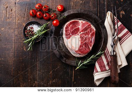 Raw Fresh Cross Cut Veal Shank For Making Osso Buco And Meat Fork On Dark Wooden Background