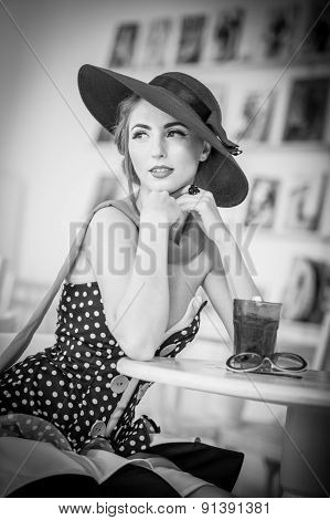 Fashionable attractive lady with hat and scarf sitting in restaurant, indoor shot. Young woman