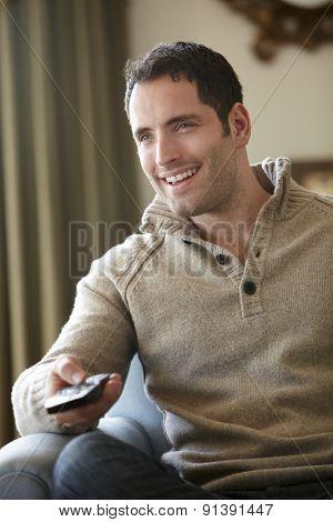 Young man watching television at home