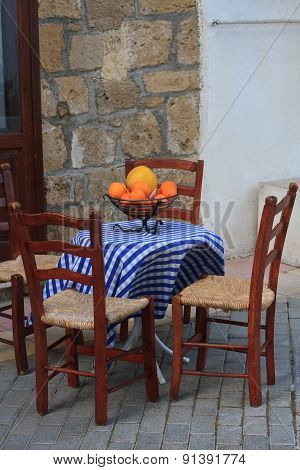 A Small Outdoor Cafe And A Bowl Of Fruit On The Table