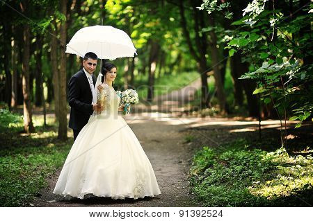 Wedding Couple At The Green Forest Under Umbrella