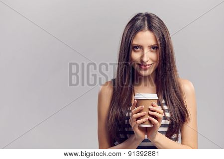 Woman drinking hot drink from disposable paper cup