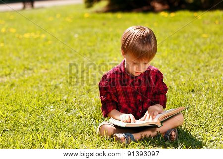 Little boy sitting on grass and reading book