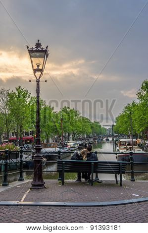 Lovers Sit Together At Twilight Overlooking A Canal In Amsterdam