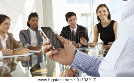Close Up Of Businessman Using Mobile Phone During Board Meeting Around Glass Table