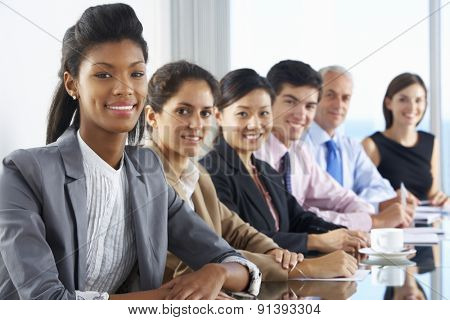 Line Of Business People Listening To Presentation Seated At Glass Boardroom Table