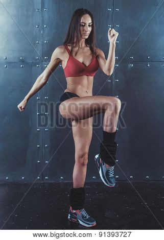Portrait of muscular active athlete woman standing looking forward lifting up leg in hands doing exe