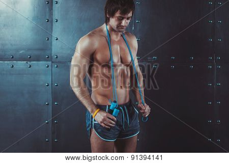 Fitness model muscular man with skipping jumping rope around his neck copy space healthy lifestyle b