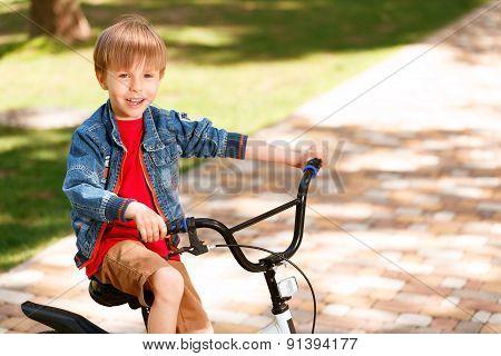 Small smiling boy riding bike.