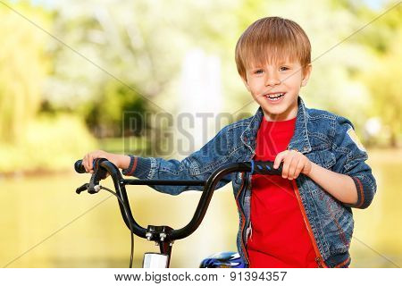 Close up of smiling boy standing near bike