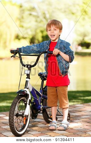 Small smiling boy standing next to bike
