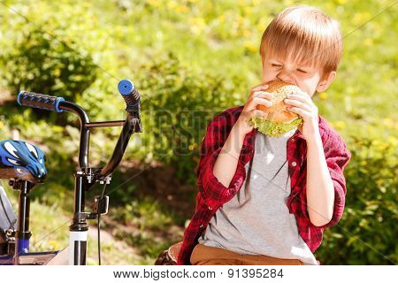 Boy biting off sandwich in park