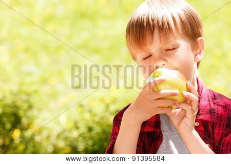 Close up of little boy biting off apple