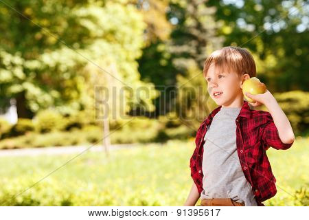 Boy going to throw apple in park.