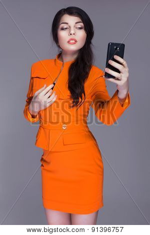 Beautiful Brunette Caucasian Woman In Orange Stylish Buisness Suit Make Selfie On The Phone. Grey Ne