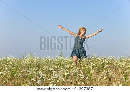 The happy young woman jumps in the field of camomiles