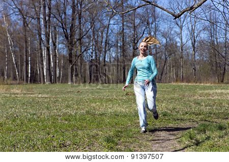 The woman runs on the track in the spring wood