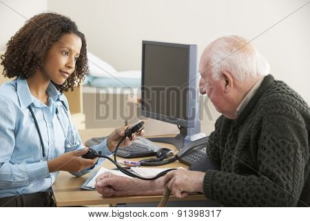 Young female Doctor taking senior man's blood pressure