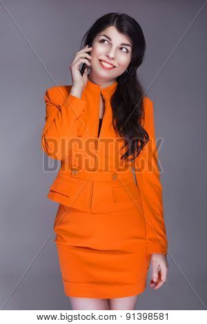 Beautiful Brunette Caucasian Woman In Orange Stylish Buisness Suit Talking On The Phone. Grey Neutra