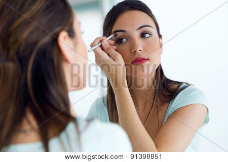 Beautiful Young Woman Making Make-up Near Mirror.