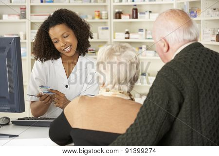 Pharmacist in pharmacy with senior couple