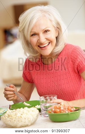 Mid age woman eating meal