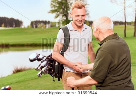 Young and old golf players shaking hands
