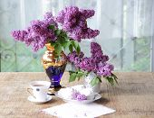 foto of fragile  - Tea to drink black tasty a cup porcelain fragile white dark blue a saucer a plate a zephyr pink sweet appetizing a vase gold a bouquet a lilac magnificent beautiful bright gentle a brush a branch leaves green aroma openwork a cloth a table wooden the hous - JPG