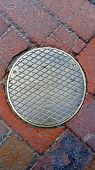 pic of manhole  - Manhole cover on an old red brick road - JPG