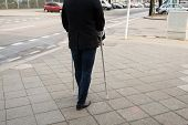image of crutch  - Rear View Of A Man Walking On Street Using Crutches - JPG